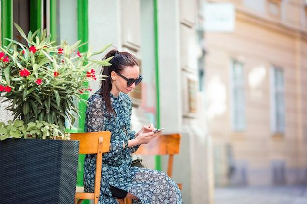 Kobieta rozmawia przez jej smartphone w mieście. młody atrakcyjny turysta outdoors w włoskim mieście Premium Zdjęcia