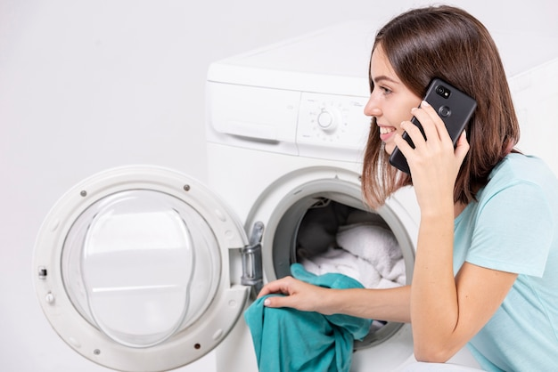 Kobieta Rozmawia Przez Telefon Podczas Prania Darmowe Zdjęcia