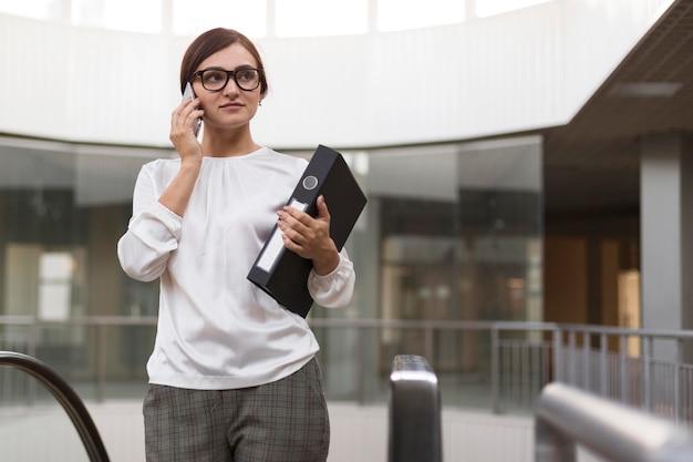 Kobieta Rozmawia Przez Telefon Trzymając Segregator Premium Zdjęcia