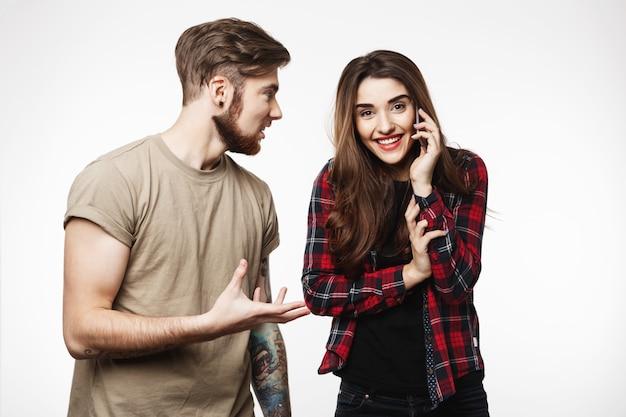 Kobieta Rozmawia Przez Telefon, Uśmiechając Się Radośnie Obok Przyjaciela Darmowe Zdjęcia