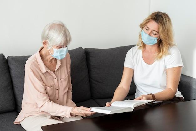 Kobieta Rozmawia Ze Starszą Kobietą Przy Książce W Domu Opieki Premium Zdjęcia