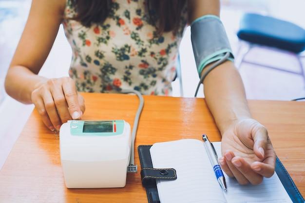 Kobieta sama stosująca test ciśnienia krwi. Premium Zdjęcia