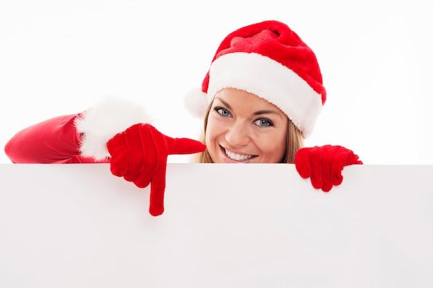Kobieta Santa, Wskazując Na Pustą Tablicę Darmowe Zdjęcia