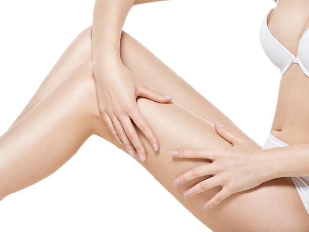 Kobieta ściska Cellulit Na Nogach Na Białej ścianie Darmowe Zdjęcia