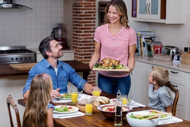 Kobieta serwująca jedzenie do swojej rodziny w kuchni Premium Zdjęcia