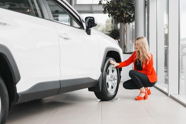 Kobieta siedząca obok białego samochodu i dotykająca koła. Premium Zdjęcia