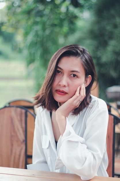 Kobieta siedzi na drewnianym krześle w restauracji Premium Zdjęcia