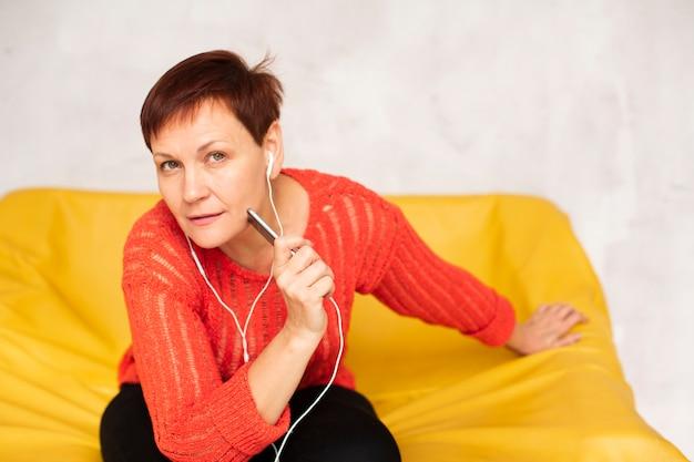 Kobieta siedzi na kanapie i patrząc na fotografa Darmowe Zdjęcia