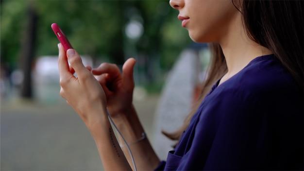 Kobieta siedzi na ławce i przy użyciu smartfona. zamknij widok Darmowe Zdjęcia