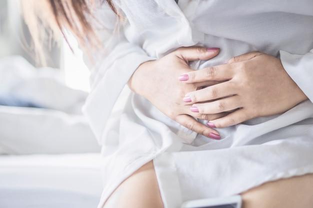 Kobieta Siedzi Na łóżku Cierpi Na Ból Brzucha Premium Zdjęcia