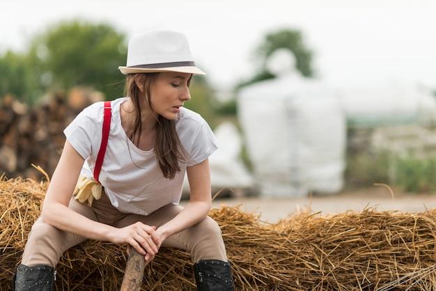 Kobieta Siedzi Na Słomie W Gospodarstwie Darmowe Zdjęcia