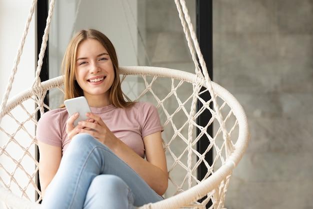Kobieta siedzi obok okna, trzymając telefon Darmowe Zdjęcia