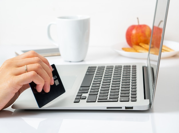 Kobieta siedzi przy stole w domu i patrząc na laptopa, zapłacić za zakupy kartą kredytową Premium Zdjęcia