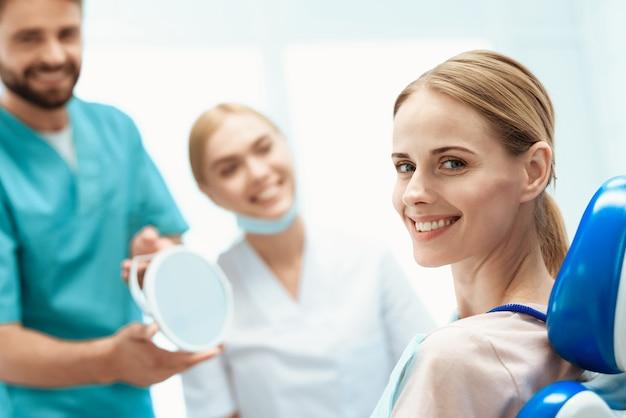 Kobieta siedzi w gabinecie dentystycznym na fotelu. Premium Zdjęcia
