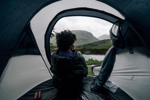 Kobieta Siedzi W Namiocie, Podczas Gdy Pada Deszcz Premium Zdjęcia