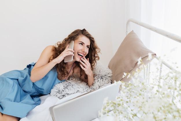 Kobieta Siedzi W Pomieszczeniu Na łóżku Rozmawia Przez Telefon. Patrząc Na Bok. Darmowe Zdjęcia
