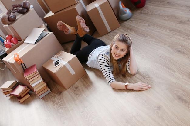 Kobieta Skończyła Pakowanie ładunków I Leży Na Podłodze I Uśmiecha Się Darmowe Zdjęcia