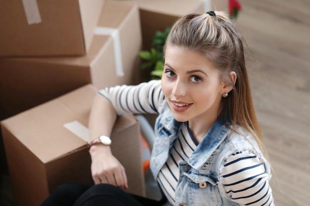 Kobieta Skończyła Pakowanie ładunków I Siedzi Obok Pudeł Darmowe Zdjęcia