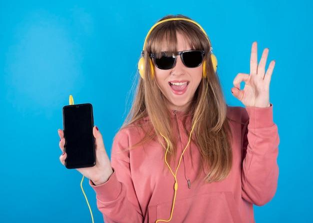 Kobieta Słucha Muzyki Ze Słuchawkami I Okularami Przeciwsłonecznymi Premium Zdjęcia