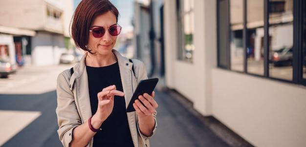 Kobieta spaceru na ulicy i pisania tekstu masaż na smartfonie Premium Zdjęcia