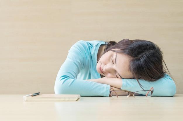 Kobieta spała leżąc na biurku po tym, jak próbowała od czytania książki w czasie odpoczynku Premium Zdjęcia