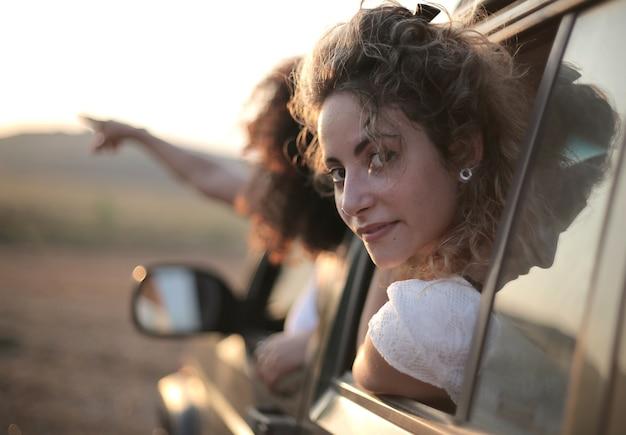 Kobieta Spoglądająca Przez Okno Samochodu Za Drugą, Wskazującą Palcem Darmowe Zdjęcia
