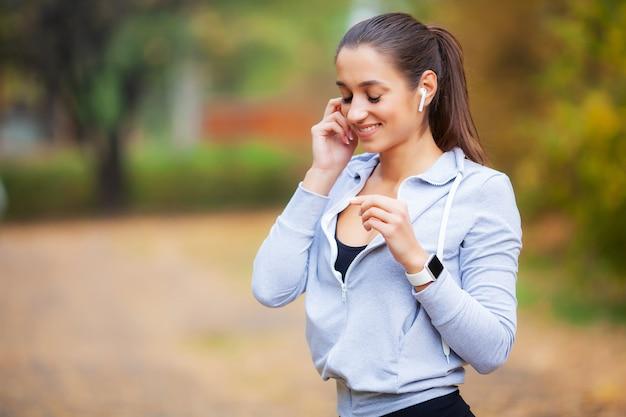 Kobieta sportowa po ćwiczeniach sportowych w środowisku miejskim Premium Zdjęcia