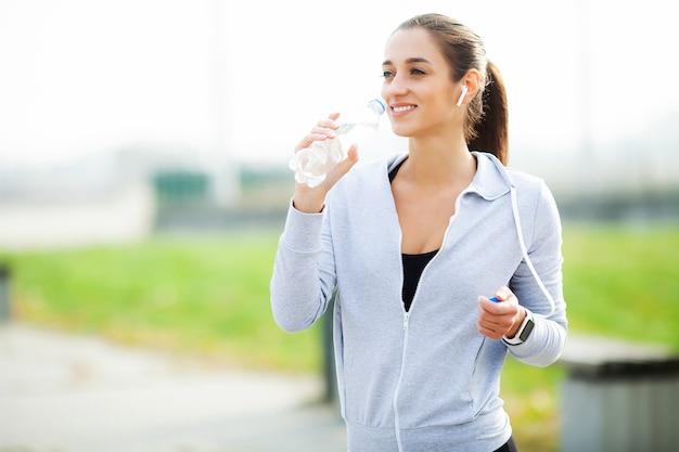 Kobieta sportowa po ćwiczeniach sportowych w środowisku miejskim. Premium Zdjęcia