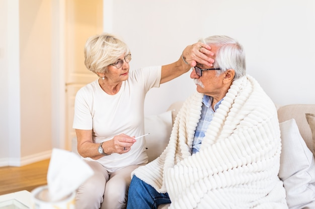 Kobieta Sprawdza Temperaturę Gorączki Starszego Mężczyzny Premium Zdjęcia