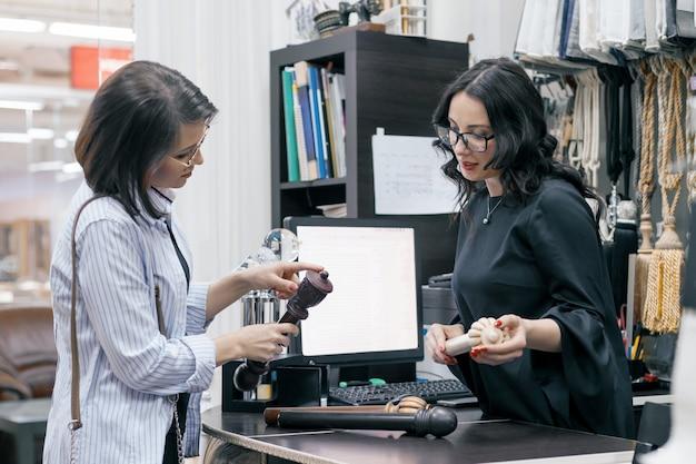 Kobieta sprzedawca rozmawia z kupującym w sklepie tkanin i akcesoriów do zasłon Premium Zdjęcia