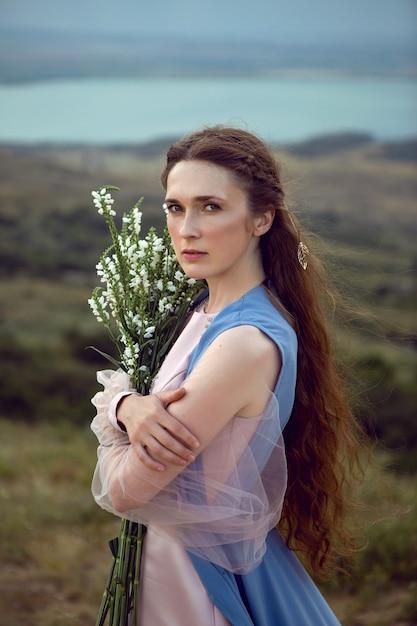 Kobieta Stoi Na Górskim Klifie W Niebieskiej Długiej Sukni Latem Premium Zdjęcia