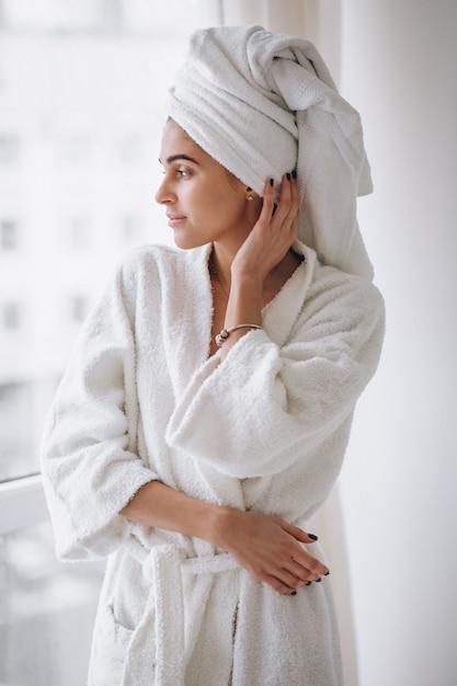 Kobieta stoi przy oknie w szlafrok Darmowe Zdjęcia
