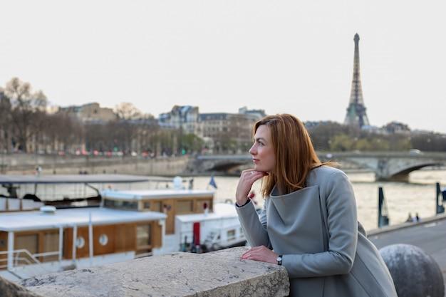 Kobieta Stoi Sama W Pobliżu Rzeki I Wieży Eiffla W Paryżu Premium Zdjęcia