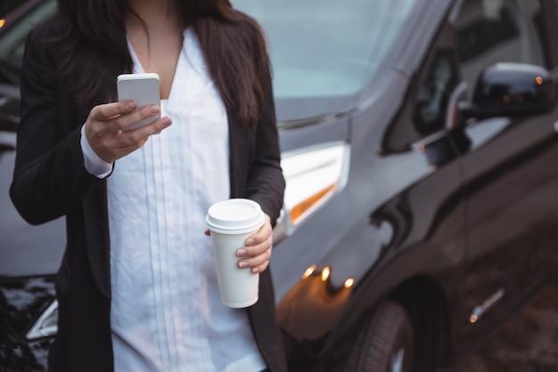 Kobieta Stojąca Obok Samochodu I Przy Użyciu Telefonu Komórkowego Darmowe Zdjęcia