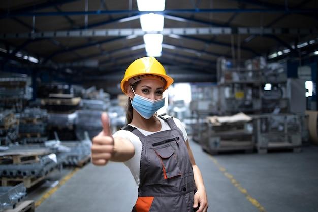 Kobieta Stojąca W Hali Fabrycznej I Pokazująca Kciuki Do Góry Podczas Noszenia Maski Higienicznej W Celu Zapobiegania Koronawirusowi Darmowe Zdjęcia