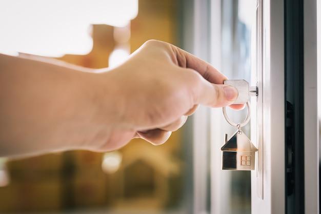 Kobieta strony wprowadzenie klucz do domu w zamek drzwi przednich domu Premium Zdjęcia