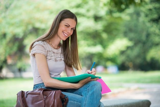 Kobieta studiuje siedząc na zewnątrz Premium Zdjęcia