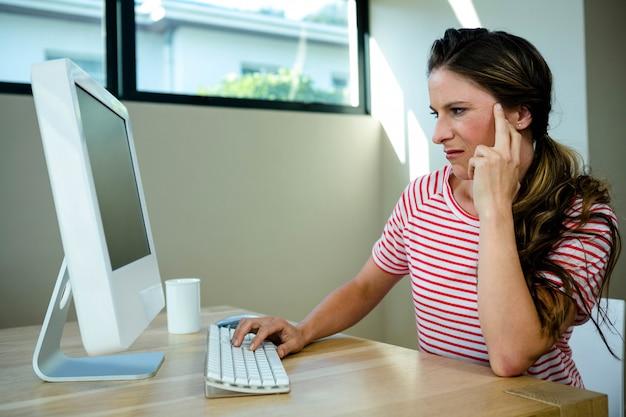 Kobieta Szuka Niezadowolonego, Siedząc Przy Biurku Na Swoim Komputerze Premium Zdjęcia