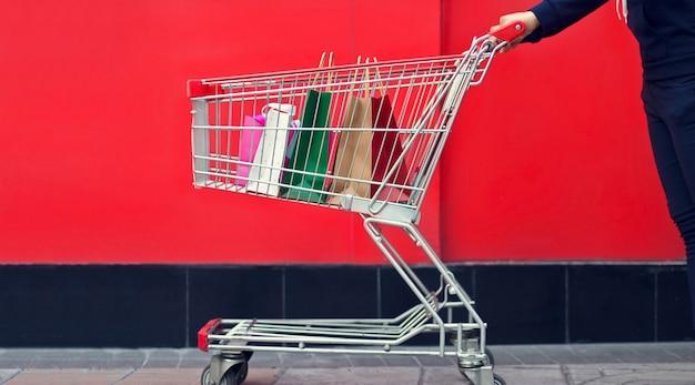 Kobieta torba na zakupy w tramwaju lub wózek na zakupy na czerwieni ścianie centrum handlowego backgrou Premium Zdjęcia
