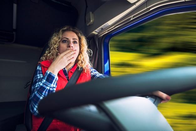 Kobieta Truckerka Ziewająca Ze Zmęczenia I Nudy Podczas Prowadzenia Ciężarówki Darmowe Zdjęcia