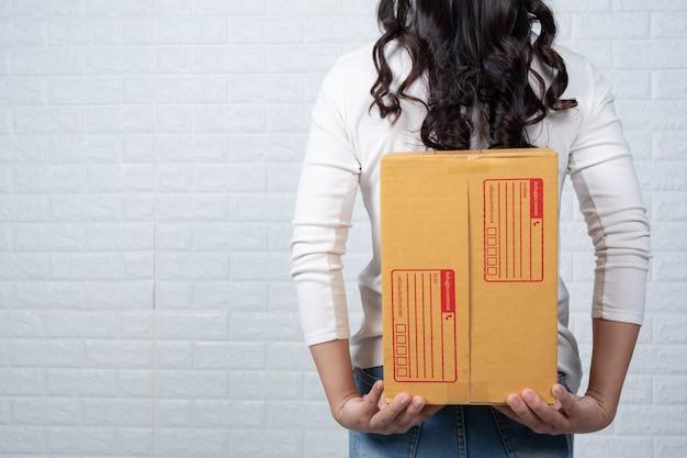 Kobieta trzyma brązową skrzynkę pocztową wykonał gesty z języka migowego. Darmowe Zdjęcia