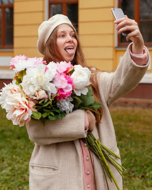 Kobieta Trzyma Bukiet Kwiatów Na Zewnątrz Wiosną I Przy Selfie Darmowe Zdjęcia