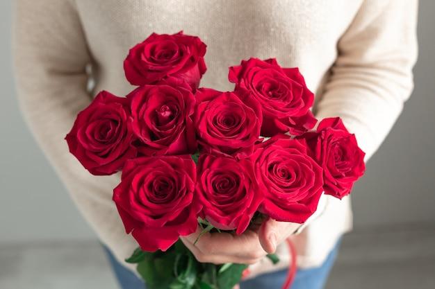 Kobieta Trzyma Bukiet świeżych Kwiatów Kwitnących Czerwonych Róż Premium Zdjęcia