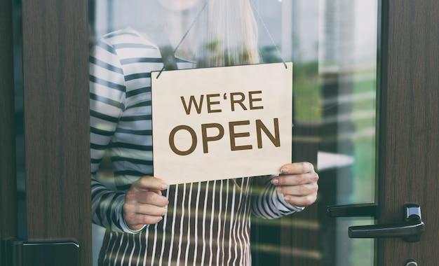 Kobieta Trzyma Drewniany Znak Z Napisem: Jesteśmy Otwarci Premium Zdjęcia
