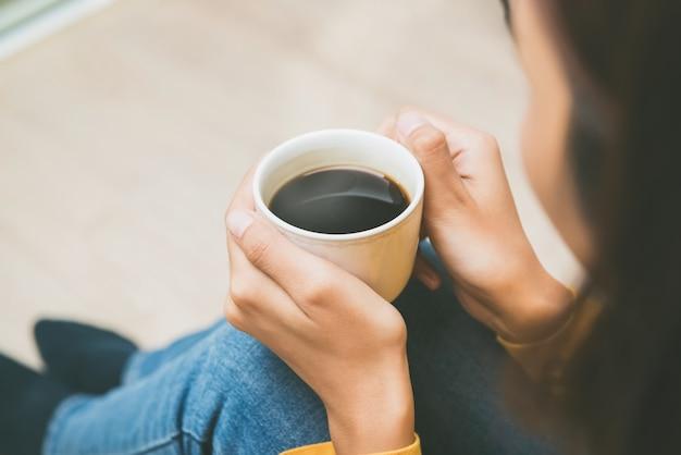 Kobieta trzyma filiżankę gorąca czarna kawa relaksuje w domu Premium Zdjęcia