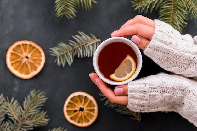 Kobieta Trzyma Filiżankę Kawy Z Plasterkami Cytryny Premium Zdjęcia
