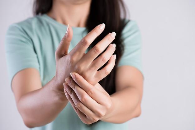 Kobieta trzyma jej kontuzji ręki nadgarstek, uczucie bólu. opieka zdrowotna i koncept medyczny. Premium Zdjęcia