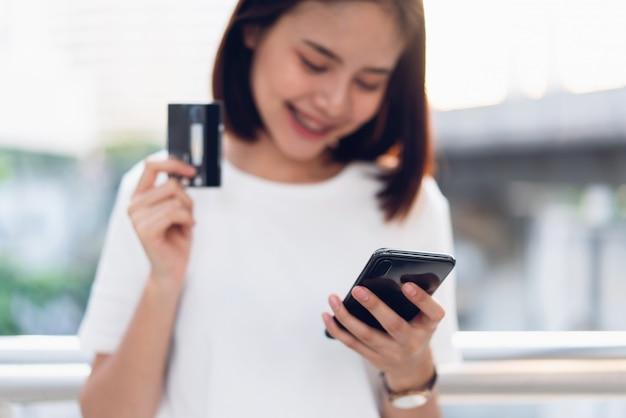 Kobieta trzyma kartę kredytową płacić online i za pomocą smartfona do sklepu za pośrednictwem strony internetowej. koncepcje zakupów online dla wygody. Premium Zdjęcia