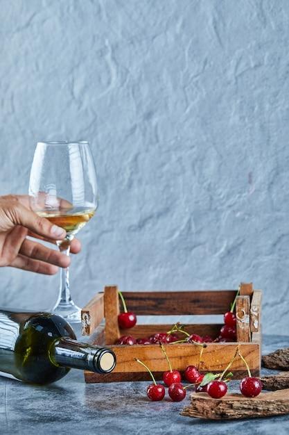 Kobieta Trzyma Kieliszek Białego Wina I Drewniane Pudełko Wiśni Na Niebieskiej Powierzchni Darmowe Zdjęcia
