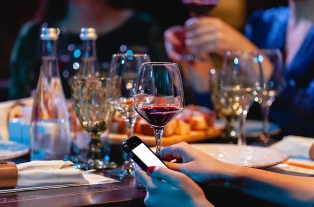 Kobieta trzyma kieliszek czerwonego wina i telefon. kolacja w restauracji, impreza Premium Zdjęcia